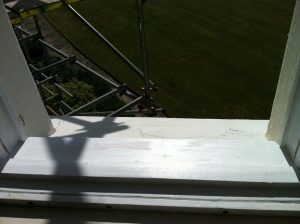 Sash window sill repaired, primed, and undercoated ready for decoration.
