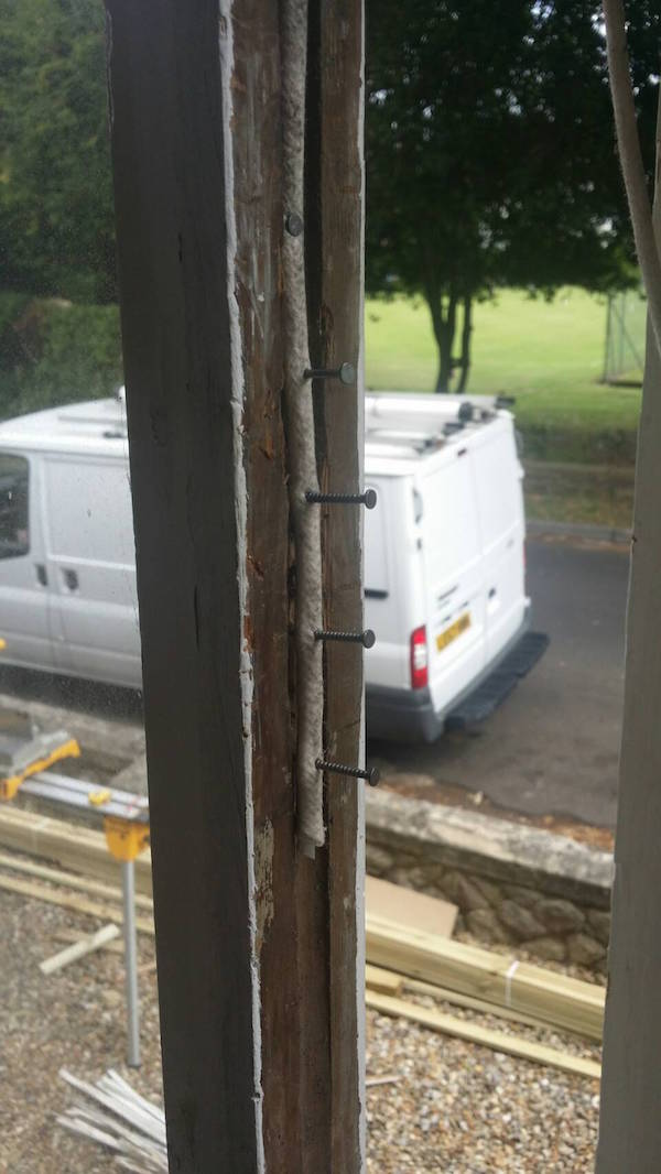 Attaching top sash after replacing a broken sash cord.