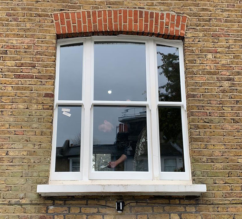 An external look at a Venetian sash window double glazed with arched head